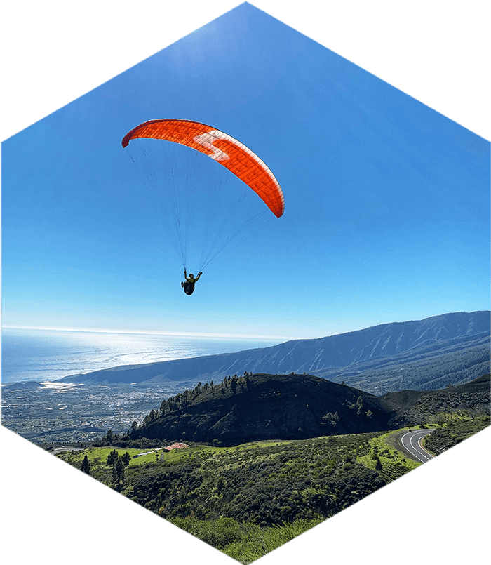 Solo paraglider with red wing flying over green mountain scenery