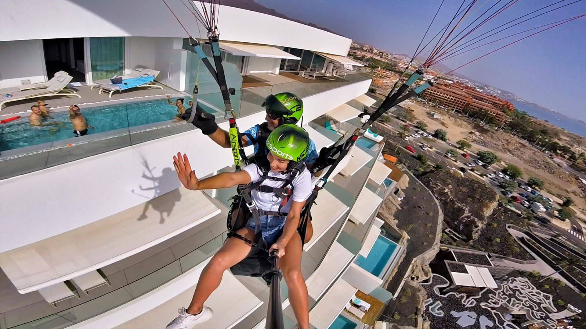 pilot and child in tandem paragliding flight passing hotel with people in swimming pool
