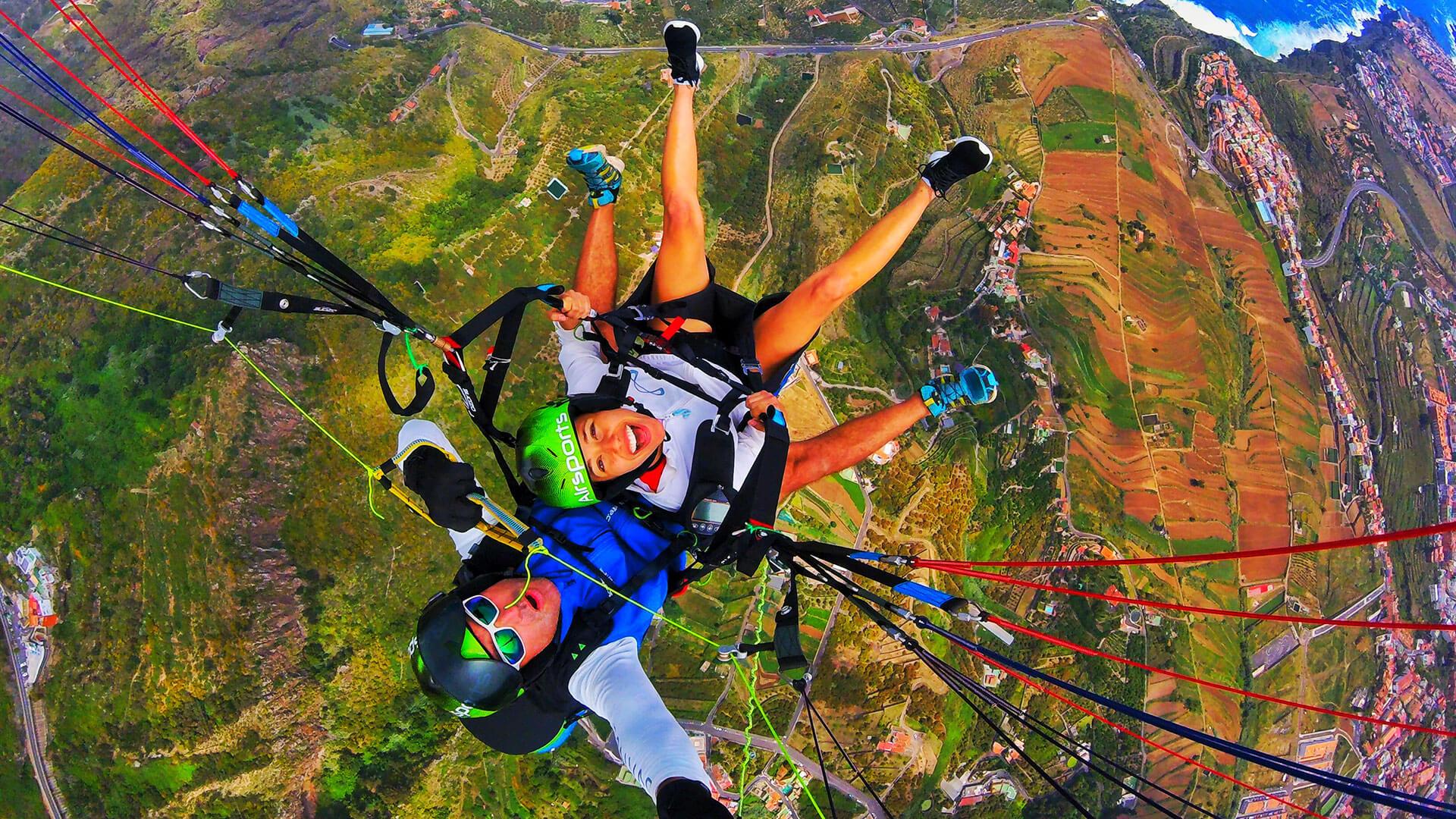 above perspective of tandem paragliders above green landscape