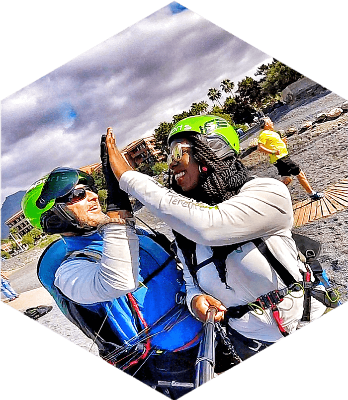 paragliding pilot and woman high five