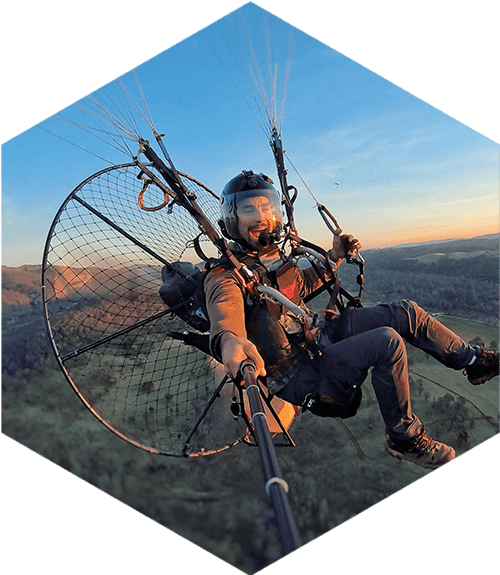 pilot paramotoring over mountains