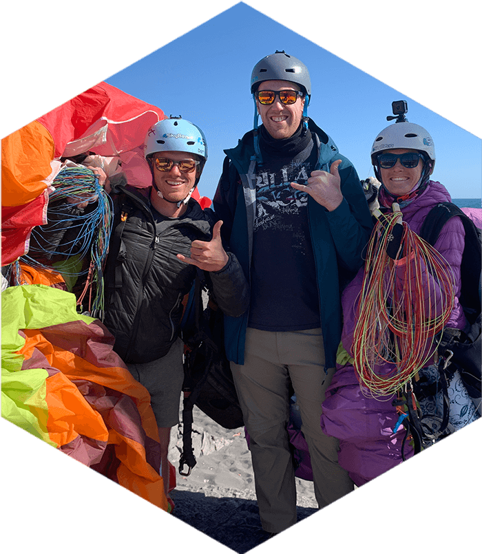 three smiling people wearing helmets and carrying paragliding kit